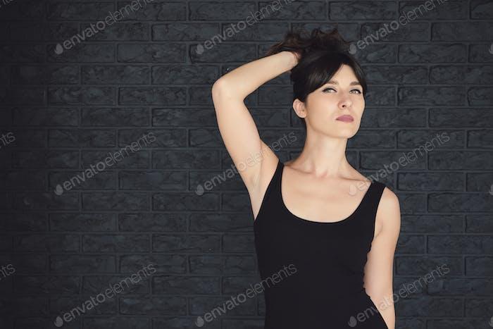 Attraktive Brünette posiert auf einem schwarzen Backsteinmauer Hintergrund