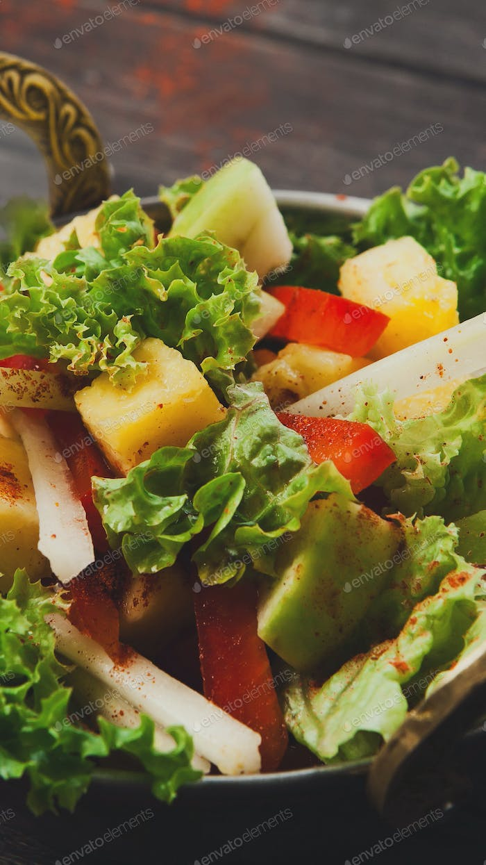 Close up of fresh fruits and vegetables salad with red spices