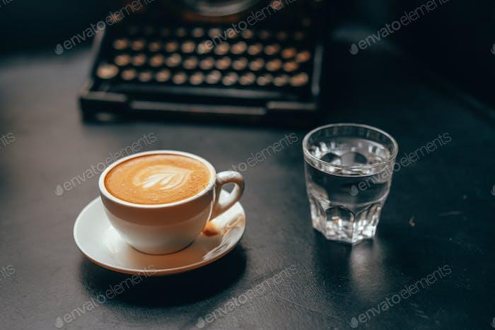 Eine Tasse Café Latte Kaffee in einer Keramiktasse und ein Glas Wasser