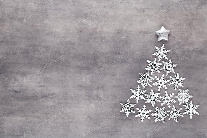 Weihnachtsbaum aus weißer Schneeflocke Dekoration auf grauem Hintergrund. Flachlage, Draufsicht