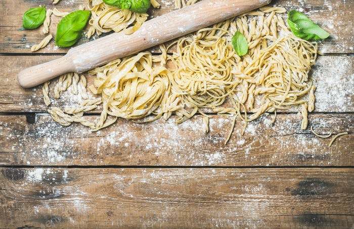 Various homemade fresh uncooked Italian pasta on wooden background