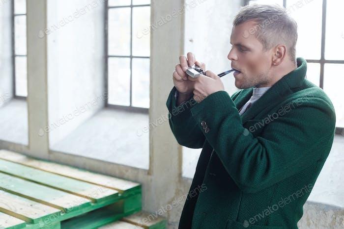 Mann raucht Pfeife.