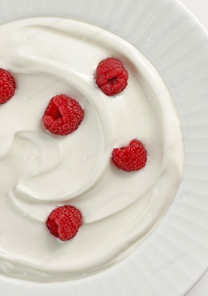 plate of greek yogurt with raspberries