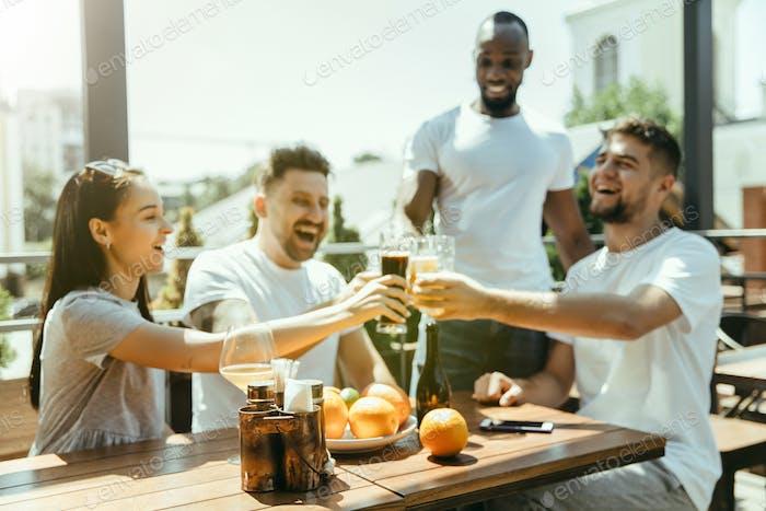 Junge Gruppe von Freunden, die Bier trinken und gemeinsam feiern