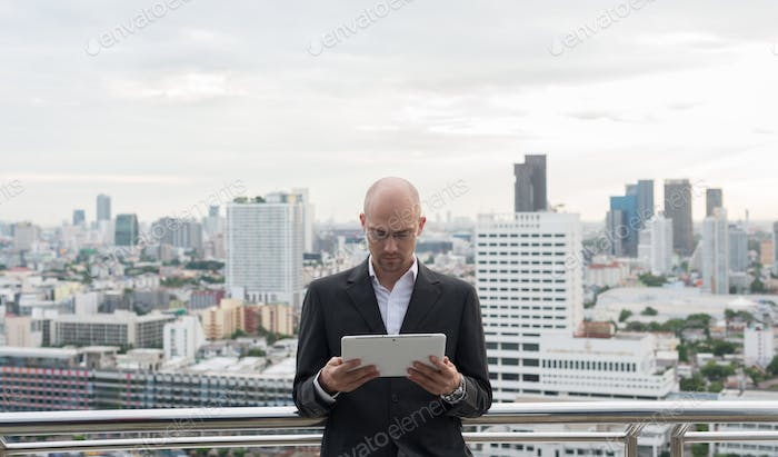 Handsome bald businessman with beard stubble against view of the city