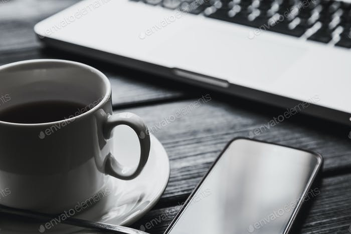 Office table with notepad, computer and tea cup