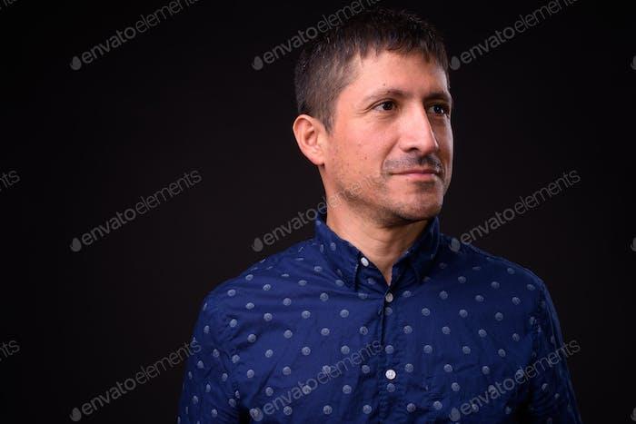 Portrait of Hispanic businessman against black background