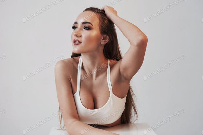 Feeling nice and calm. Portrait of seductive brunette in the studio with white background