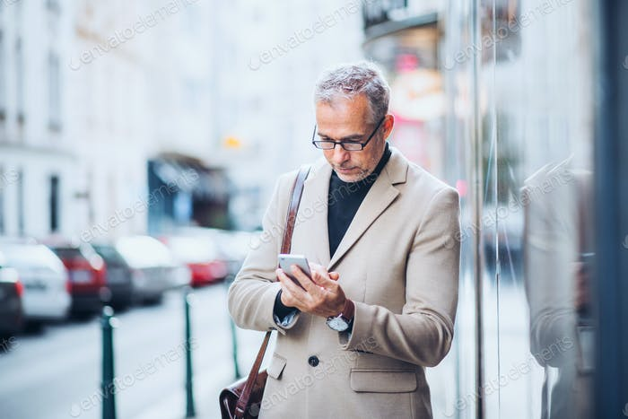 Mature businessman standing on a street in city, holding smartphone.