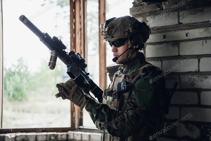 Brutal military man is sitting and cleaning and preparing his gun to the battle
