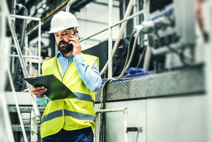 A portrait of an industrial man engineer with smartphone in a factory, working.