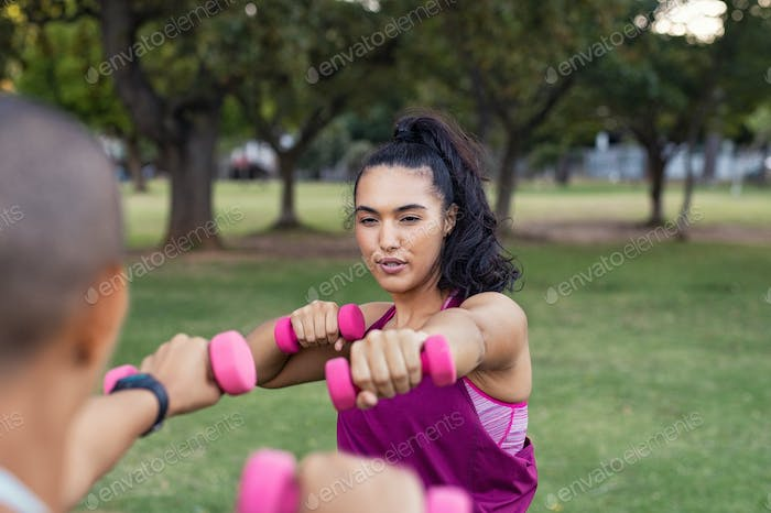 Determined fitness woman using dumbbells