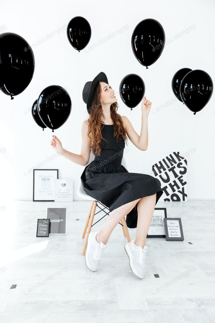 Woman sitting and holding black balloons over white background