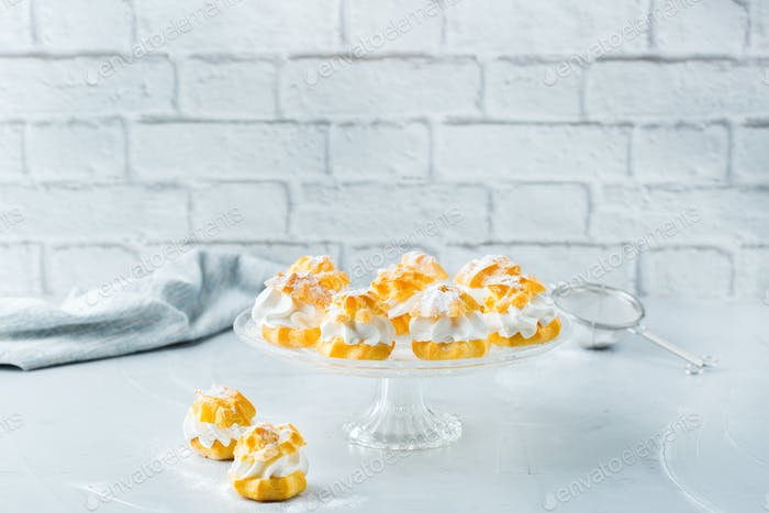 Delicious sweet profiteroles with cream on a modern kitchen table