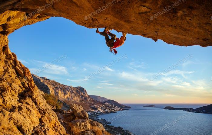 Männlicher Kletterer auf überhängenden Felsen gegen schöne Aussicht auf die Küste unten