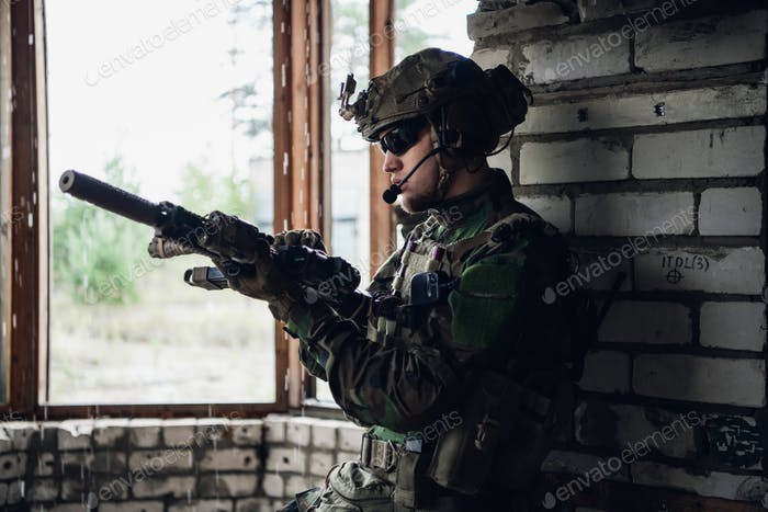 A thoughtful soldier, resting from a military operation while it is raining outside