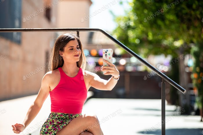 Young spanish woman taking a self photo with the mobile phone.