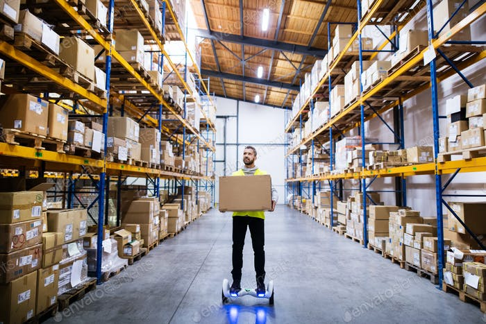 Male warehouse worker on hoverboard.