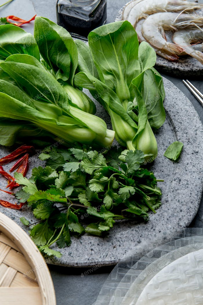 Asian cooking ingredients: rice papper, pok choy, sauces, raw shrimps. Asian food concept Chinese or
