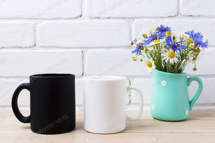 Weiße und schwarze Tasse Mockup mit Kornblume und Gänseblümchen