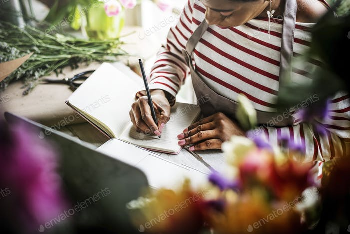 Woman Sitting Writing on Notebook in Flower Shop