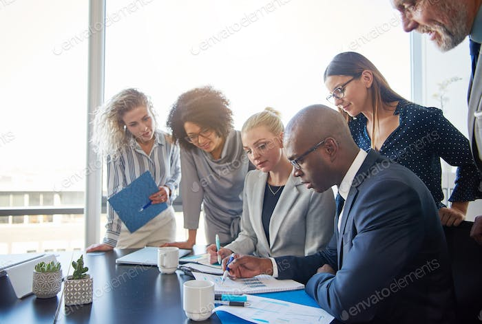 Focused group of office colleagues reading paperwork in a boardroom