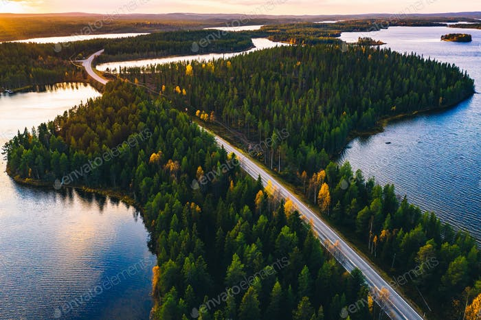 Aerial view of road in green summer forest with blue lakes at sunset in Finland