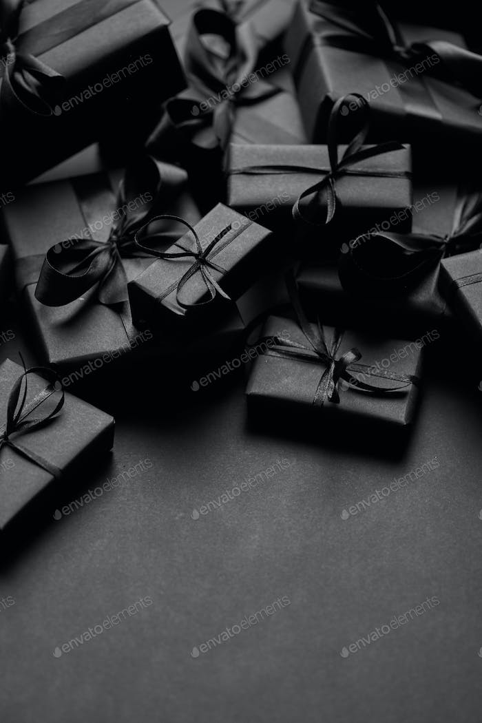 A pile various size black boxed gifts placed on stack. Christmas concept