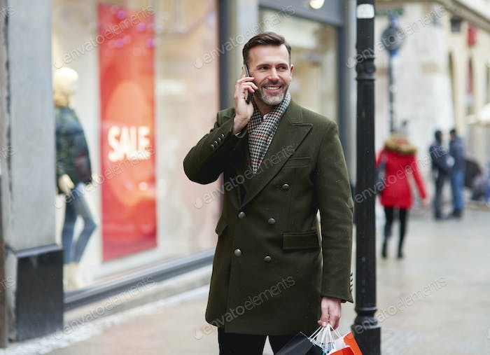Smiling man is on the phone during Christmas shopping