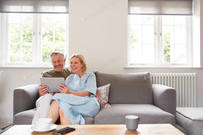 Senior Couple Sitting On Sofa In Lounge At Home Using Digital Tablet Together