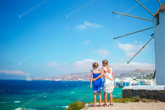 Adorable little girls with amazing view on Little Venice the most popular tourist area on Mykonos