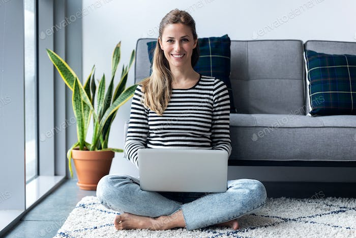 Pretty young woman looking at camera while using her laptop at home.