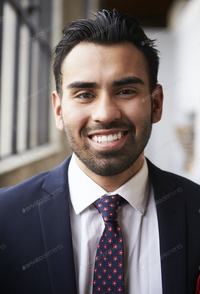 Young Hispanic businessman smiling to camera, vertical