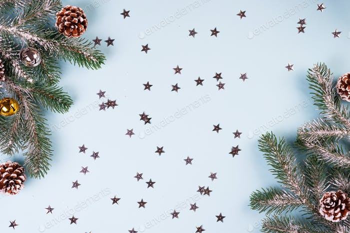 Fir tree branch with cones and snow on starry blue paper, top view