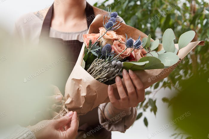 Close-up of roses flowers bouquet in a woman's hands on a blured green leaf background