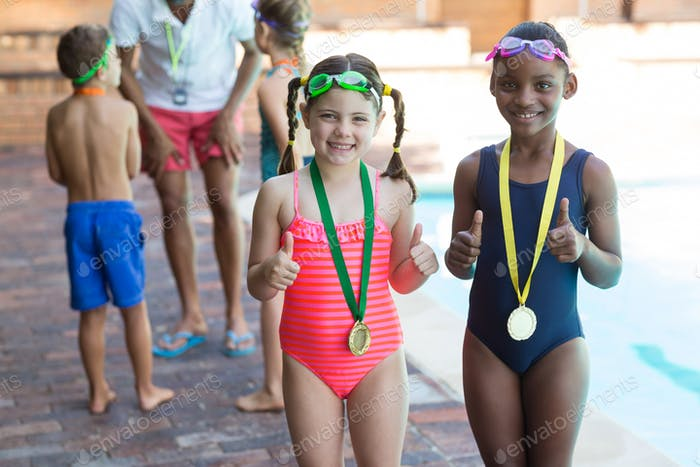 Portrait of little girls showing thumbs up at poolside