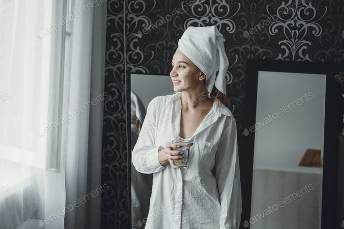 Morning daily routine, drink water Benefits. Cheerful young woman smiling and looking at the window