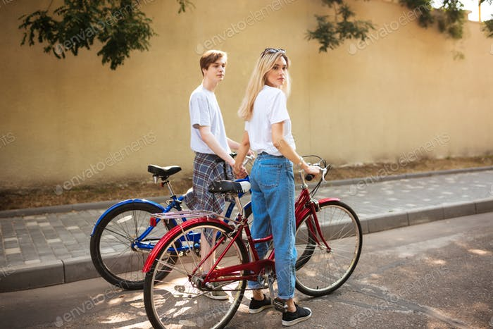 Thoughtful boy and pretty girl with blond hair standing with red and blue bicycles and holding hands