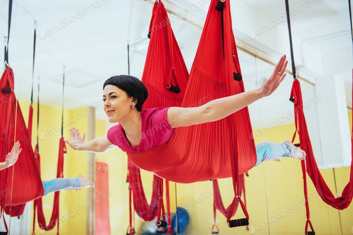 Young women doing yoga exercise or aerial yoga antigravity in the studio.