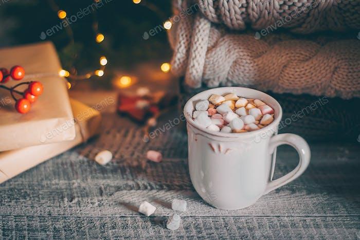 Stapel von gemütlichen gestrickten Pullover und Tasse Kaffee oder heiße Schokolade mit Marshmallow. Magie, gemütlich