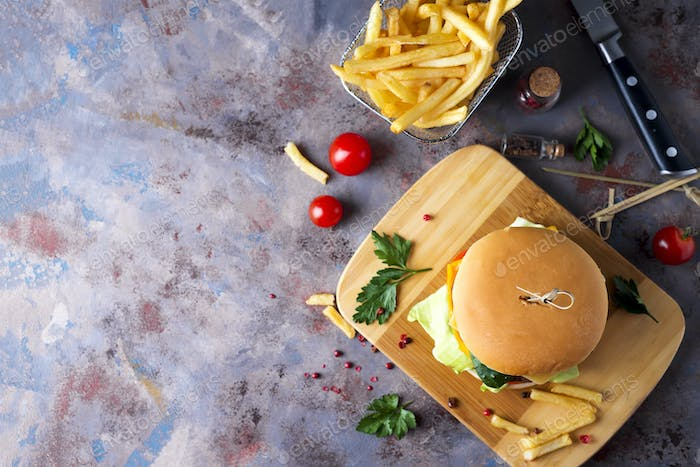 Hamburger with french fries, beer on a stone table