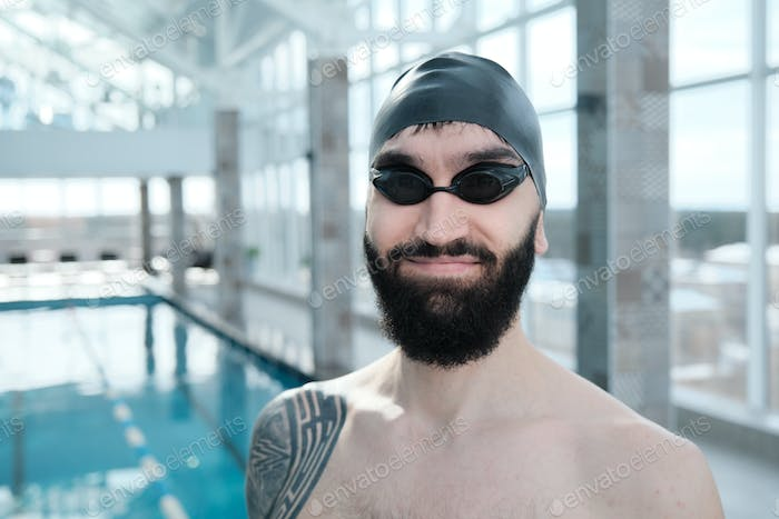 Satisfied swimmer in cap and goggles