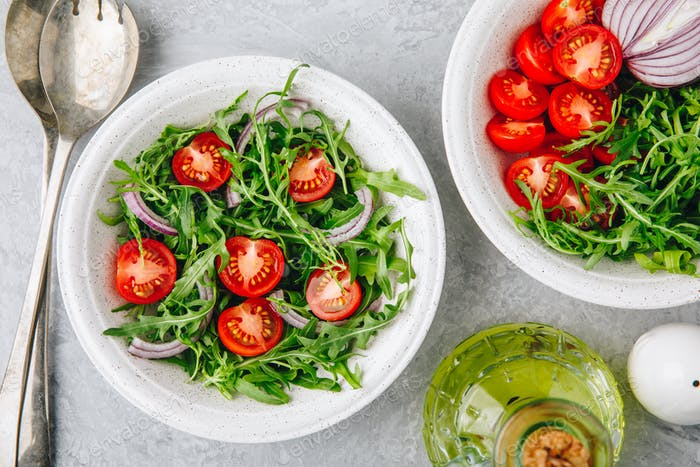 Healthy Green Fresh Arugula Salad Bowl with Tomatoes and Red Onions. Top view