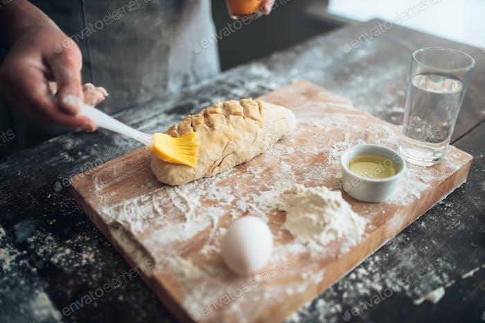 Baker hands smears butter on bread dough