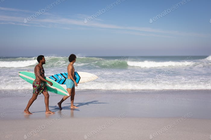Side view of young multi-ethnic men with surfboard walking at beach in the sunshine