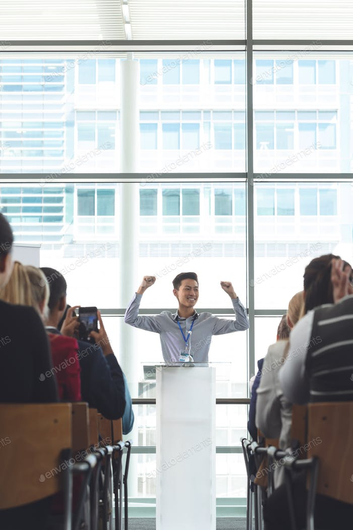 Young businessman cheering during seminar in front of business professionals sitting in office