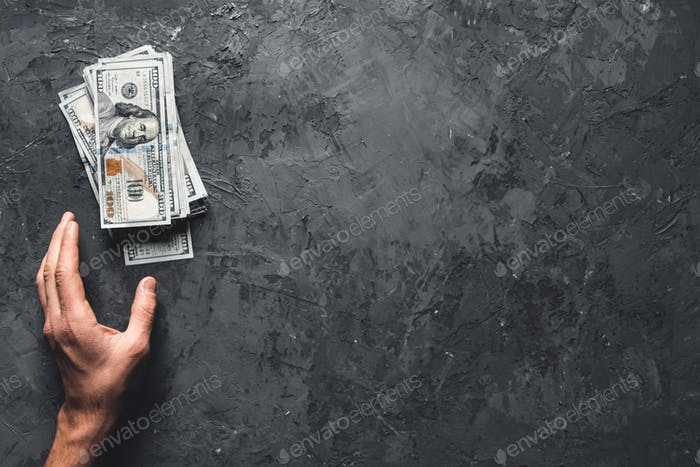 Hand holding money against dark background. Business concept, development perspective