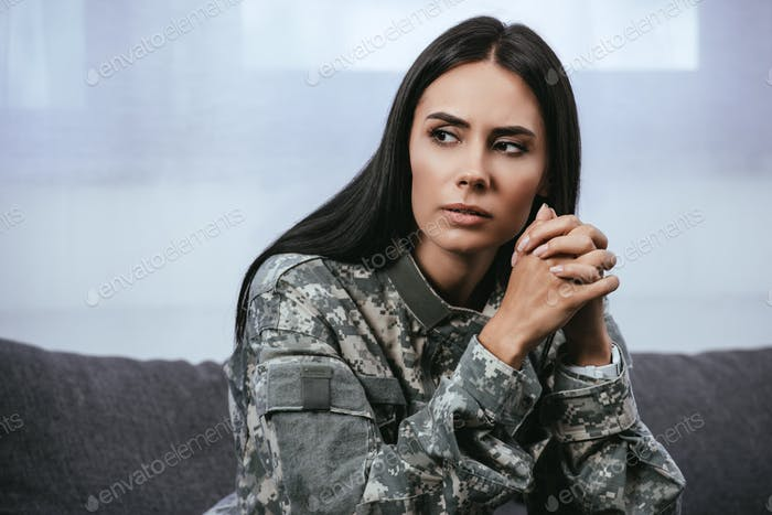 close-up portrait of thoughtful female soldier in military uniform with ptsd sitting on couch and