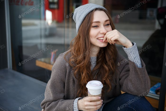 Happy woman drinking coffee-to-go and thinking in the city
