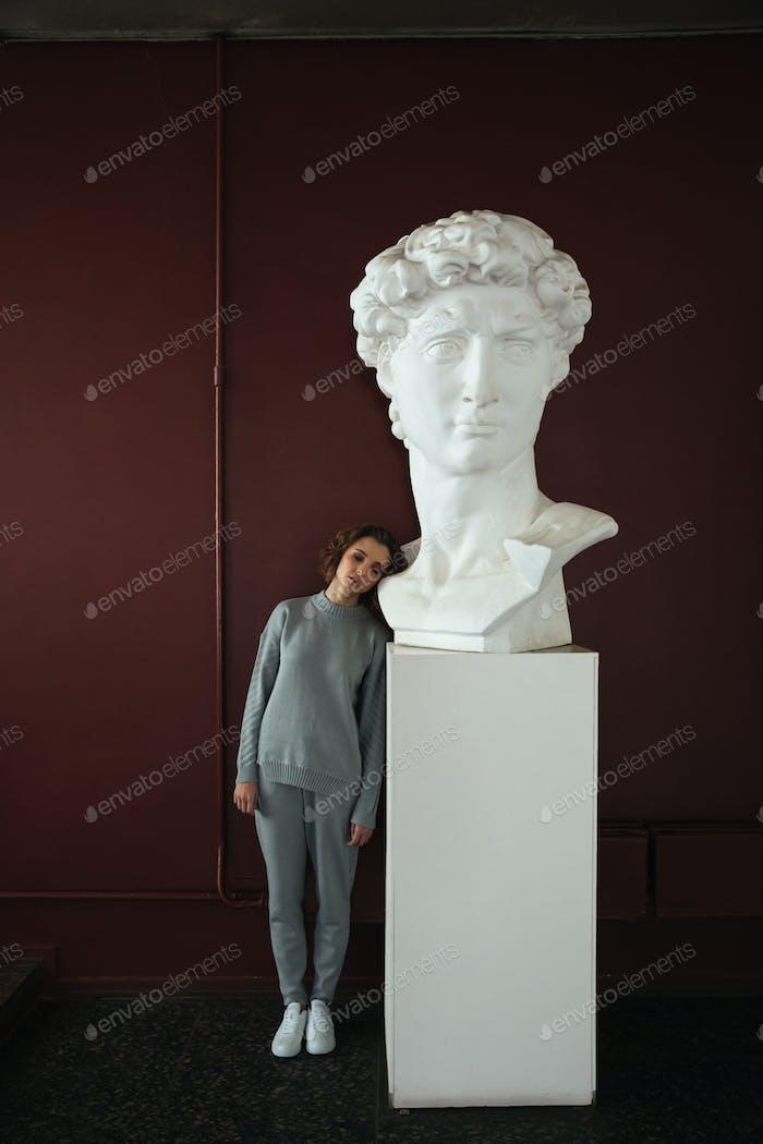 Woman standing near bust